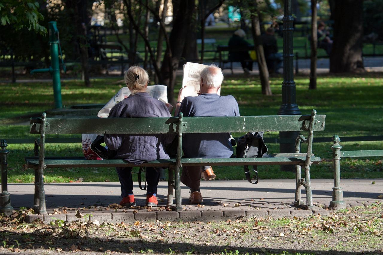 chorzy ludzie siedzący na ławkach w parku